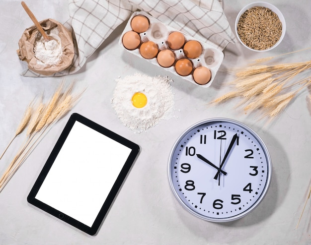 Ingrediënten voor het bakken met tablet en klok