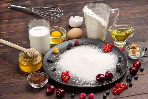 Ingrediënten voor het bakken van bessentaart. meel in zwarte plaat, cacaopoeder. maatbeker met bloem, glas melk, gebroken ei en zout, metalen garde op tafel. donker houten oppervlak. bovenaanzicht