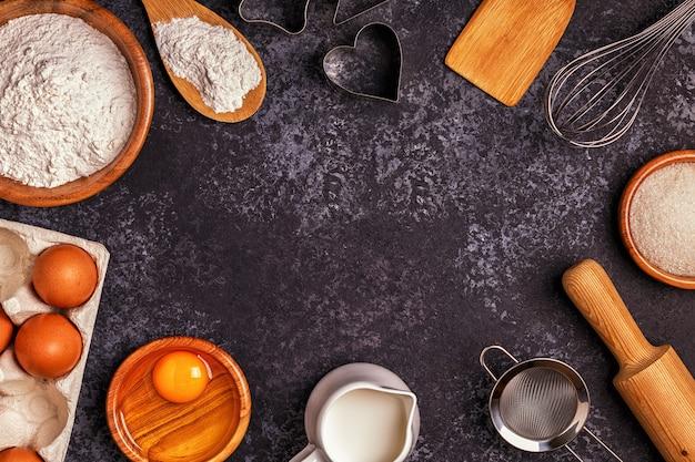 Ingrediënten voor het bakken van bloem, houten lepel, deegroller, eieren