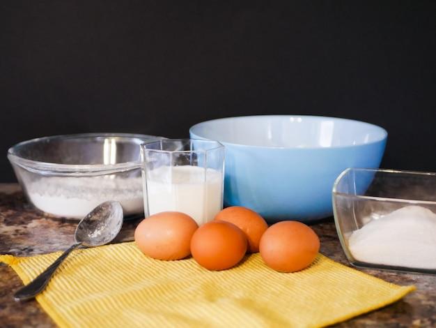 Ingrediënten voor het bakken van deeg. bloem, eieren, melk. ingrediënten bakken. lepel op een marmeren tafel. voorbereiding voor het koken.