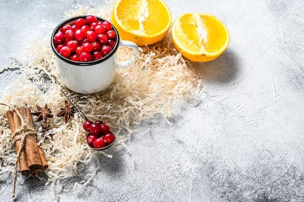 Ingrediënten voor het bakken van koekjes in de winter peperkoek, fruitcake, dranken veenbessen, sinaasappels, kaneel, specerijen kerstmisvoedsel grijs oppervlak