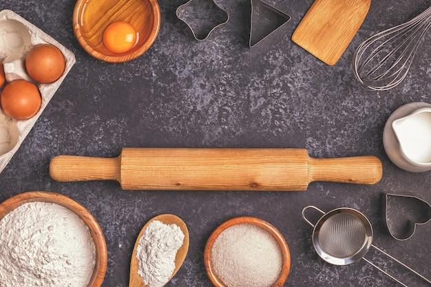 Ingrediënten voor het bakken van meel houten lepel deegroller eieren bovenaanzicht kopieerruimte