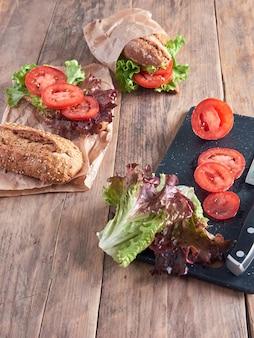 Ingrediënten voor het bereiden van een groentebaguette die op een houten tafel wordt tentoongesteld