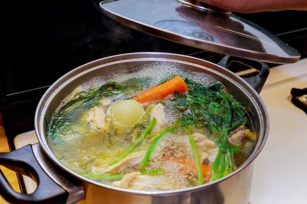 Ingrediënten voor het bereiden van kippenbot bouillon in een pot kip, uien, knolselderij, wortelen, peterselie
