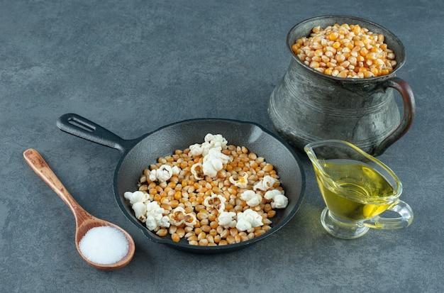 Ingrediënten voor het bereiden van zelfgemaakte popcorn op marmeren achtergrond. hoge kwaliteit foto