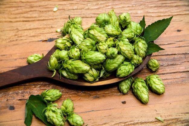 Ingrediënten voor het brouwen van bier hopbellen in houten kom en tarweoren op houten achtergrond. bierbrouwerij concept.