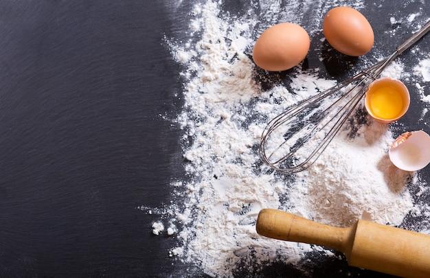 Ingrediënten voor het koken: bloem, eieren op donker