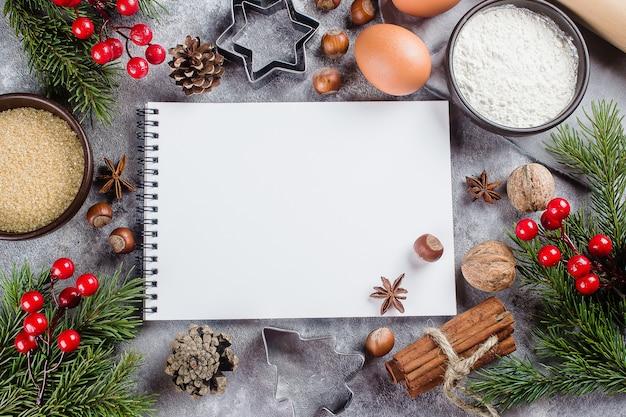 Ingrediënten voor het koken kerstmisbaksel en leeg witboeknotitieboekje op grijze steenrug