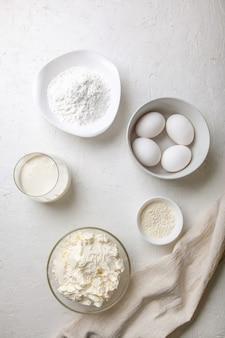 Ingrediënten voor het koken van baskische spaanse gebrande sint-sebastiaan-cheesecake. bakproducten - roomkaas, suiker, eieren, bloem en room op een licht oppervlak. recept stap voor stap flatlay bovenaanzicht.
