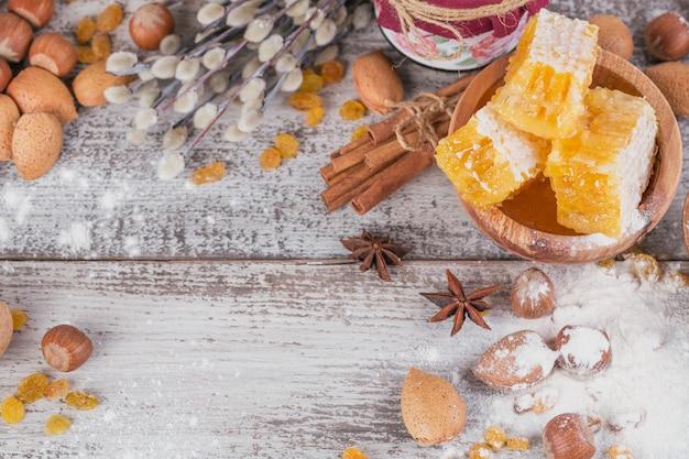 Ingrediënten voor het koken van brood of koekjes met honingraat, bloem, rozijnen, mix van noten, kruiden