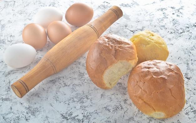 Ingrediënten voor het koken van broodjes thuis. eieren, deegroller, broodjes op een witte betonnen tafel