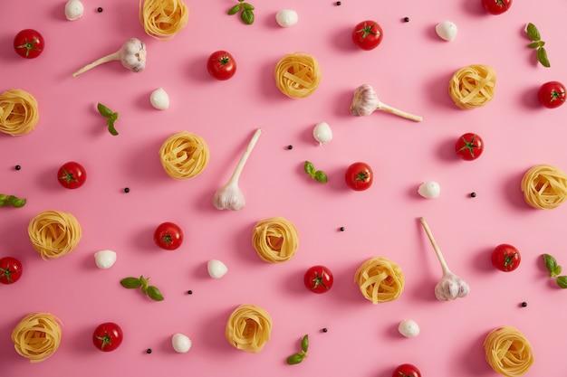 Ingrediënten voor het koken van deegwaren. boven schot van zelfgemaakte ronde deegwarenballen fettuccine, tomaten, knoflook, basilicum en mozarellakaas op roze achtergrond. selectieve aandacht. culinair. verse producten