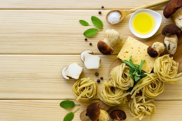 Ingrediënten voor het koken van deegwaren. fettuccine met eekhoorntjesbrood, kaas en salieblaadjes op een lichte houten achtergrond.