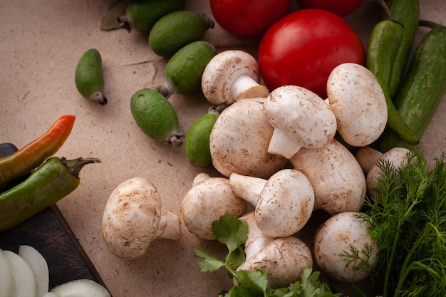 Ingrediënten voor het koken van een vegetarische maaltijd zonder vlees, rauwe champignons en komkommer op een bord