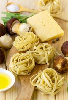 Ingrediënten voor het koken van fettuccine pasta met eekhoorntjesbrood en kaas op een houten achtergrond.