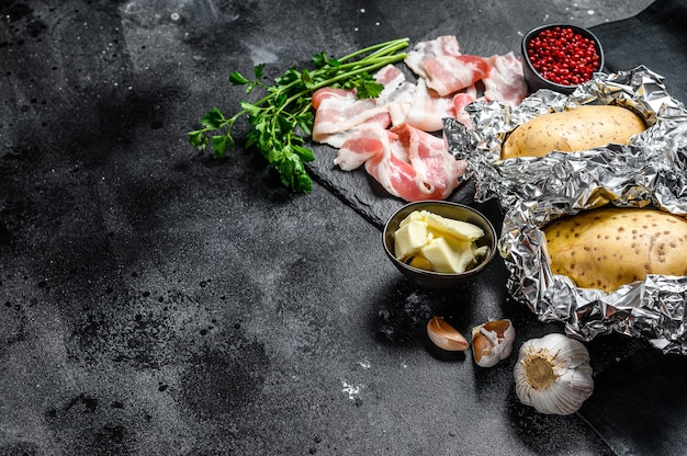 Ingrediënten voor het koken van gebakken aardappelen met spek, boter, peterselie en kaas. zwarte achtergrond
