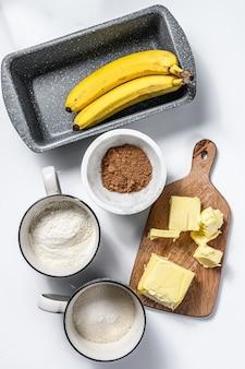 Ingrediënten voor het koken van gezond koekje. banaan, bloem, suiker en boter. witte achtergrond. bovenaanzicht.