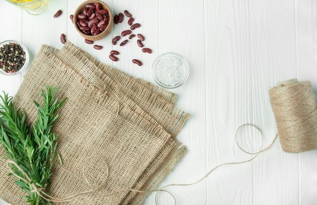 Ingrediënten voor het koken van gezond voedsel. kokende achtergrond, witte achtergrond. achtergrond met jute. kopieer ruimte achtergrond menutabel.