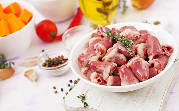 Ingrediënten voor het koken van kippenharten met pompoen en tomaten in tomatensaus. de garnering wordt geserveerd met gekookte rijst.