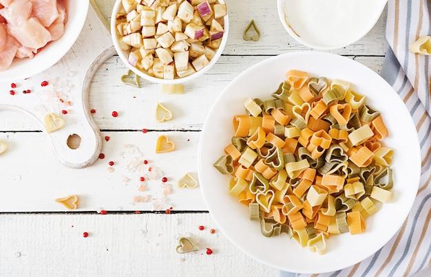 Ingrediënten voor het koken van romige pasta met kip en aubergine geserveerd in diepe plaat.
