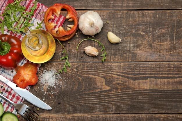 Ingrediënten voor het koken van salade. diverse groenten en kruiden wortelen, tomaten, komkommers, paprika's en rucola op een bruin houten tafel. bovenaanzicht.