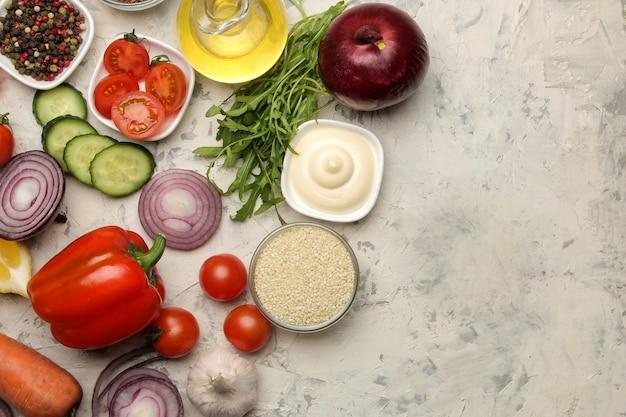 Ingrediënten voor het koken van salade. diverse groenten en kruiden wortelen, tomaten, uien, komkommers, paprika's en rucola op een lichte achtergrond. bovenaanzicht.