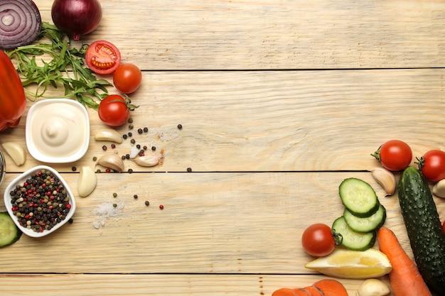 Ingrediënten voor het koken van salade. diverse groenten en kruiden wortelen, tomaten, uien, komkommers, paprika's en rucola op een natuurlijke houten tafel. bovenaanzicht.