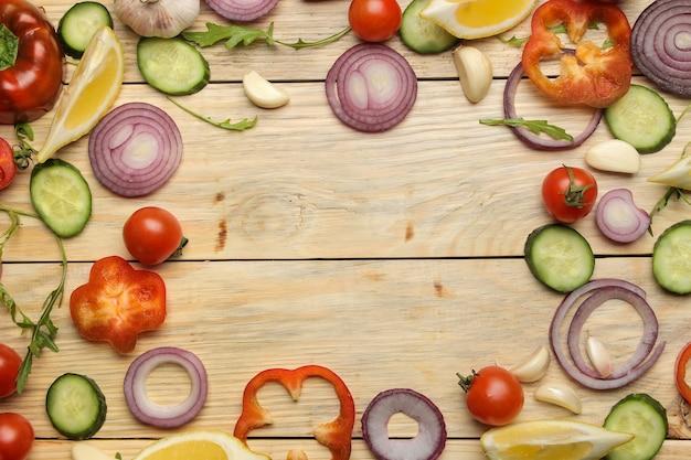 Ingrediënten voor het koken van salade. frame van verschillende groenten en kruiden wortel, tomaat, ui, komkommer, paprika en rucola op een natuurlijke houten tafel. bovenaanzicht.