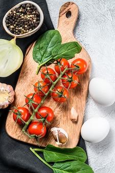 Ingrediënten voor het koken van shakshuka. eieren, uien, knoflook, tomaten, paprika's, spinazie. grijze achtergrond. bovenaanzicht.