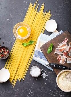 Ingrediënten voor het koken van traditionele italiaanse pastaschotel spaghetti carbonara, rauwe dooier, parmezaanse kaas, spek op houten bord op zwarte rustieke stenen achtergrond