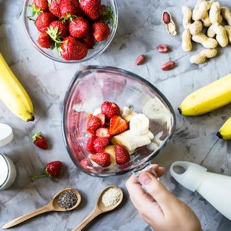 Ingrediënten voor het maken van aardbei-banaan smoothies op een grijze tafel
