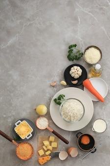 Ingrediënten voor het maken van arancini koken op een achtergrond van wit grijs marmer. kaas, rijst, melk, ei, wortel, peterselie, boter, knoflook, broodkruim en parmezaanse kaas