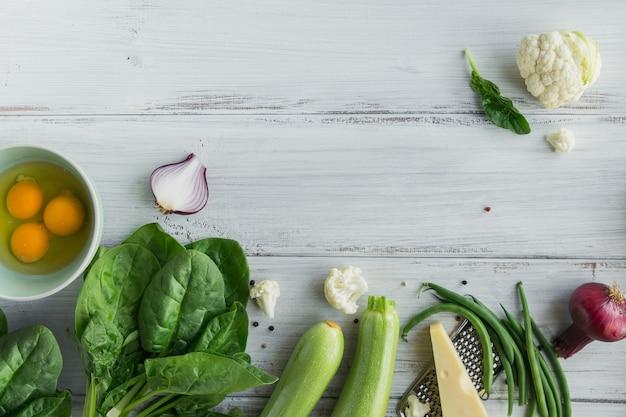 Ingrediënten voor het maken van gezond veganistisch eten. bloemkool, courgette, rode ui, sperziebonen, eieren, kaas en spinazieblaadjes voor het maken van groentefrittata