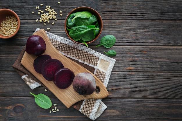 Ingrediënten voor het maken van gezond veganistisch eten met gesneden rode biet, spinazie en pijnboompitten. schoon eten, vegetarisch voedselconcept. plat leggen