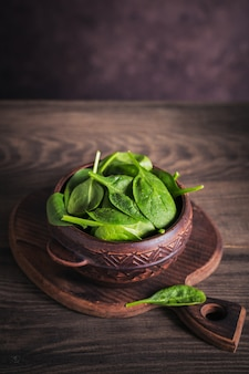 Ingrediënten voor het maken van gezond veganistisch eten met gesneden rode biet. verse babyspinazie in een kleikom op rustieke houten oppervlakte. schoon eten, vegetarisch voedselconcept