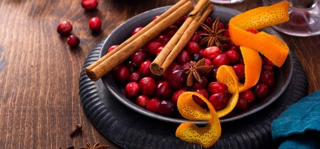Ingrediënten voor het maken van glühwein met veenbessen. sinaasappel, kaneel, cranberrybessen, kruidnagel, anijs en suiker. kerst sfeervol retro concept. plaats voor tekst