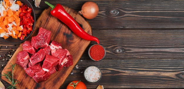 Ingrediënten voor het maken van goulash of stoofpot, stoofpot of gyuvech. bovenaanzicht van rauw rundvlees, kruiden, specerijen, paprika, groenten op zwarte houten tafel