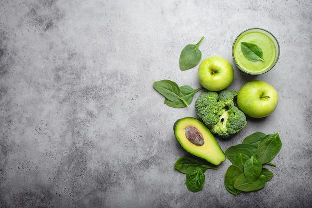 Ingrediënten voor het maken van groene gezonde smoothie met broccoli, appels, avocado, spinazie, stenen achtergrond. schoon eten, detox plan, dieet, gewichtsverlies concept. close-up, bovenaanzicht, ruimte voor tekst