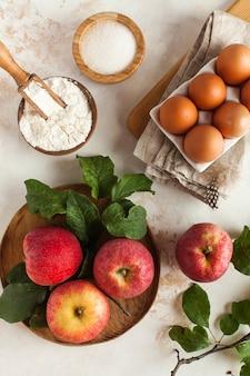Ingrediënten voor het maken van herfsttaart, charlotte zoals appels, bloem, eieren, suiker.