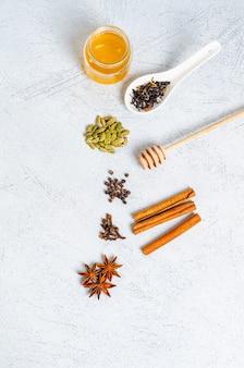 Ingrediënten voor het maken van indiase traditionele masala-theedrank. kaneel, kardemom, anijs, honing, kruidnagel, droge thee op een lichte tafel. uitzicht van boven. kopieer ruimte voor tekst, plat leggen. verticale oriëntatie