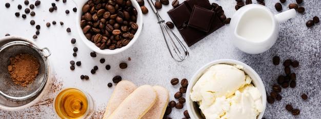 Ingrediënten voor het maken van italiaanse desserttiramisu, savoiardi, mascarpone, cacaopoeder en chocolade op licht beton