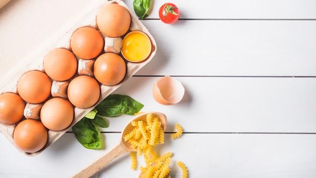 Ingrediënten voor het maken van italiaanse fusilli pasta op witte houten plank