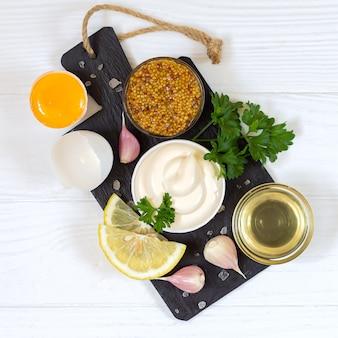Ingrediënten voor het maken van mayonaisesaus op stenen bord bovenaanzicht