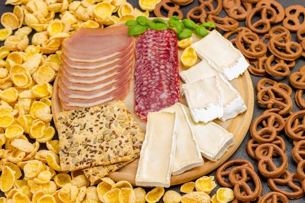 Ingrediënten voor het maken van ontbijt: spek, kaas, granen, koekjes, basilicum