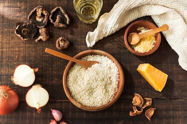 Ingrediënten voor het maken van risotto-paddestoelen op rustieke houten tafel