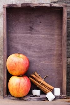 Ingrediënten voor het maken van rustgevende appel en kaneel thee in een lade op een houten tafel. detox-concept, antidepressivum. mooi stilleven