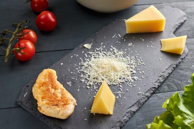Ingrediënten voor het maken van salade. stuk en geraspte parmezaanse kaas op een zwarte serveerschaal, kerstomaatjes, geroosterde kip en slablaadjes.