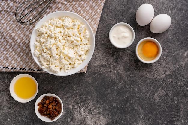 Ingrediënten voor het maken van zelfgemaakte cheesecakes op een stenen achtergrond. bovenaanzicht, kopieer ruimte.