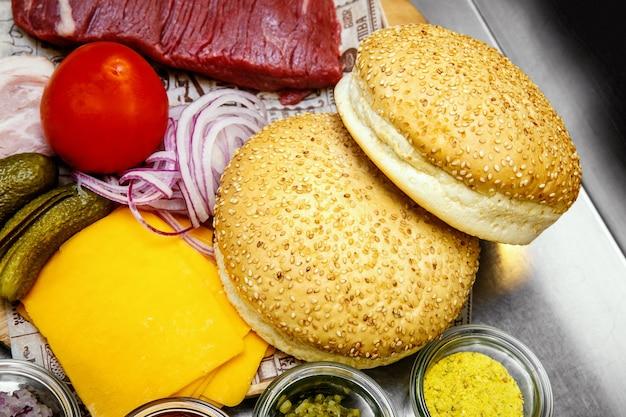 Ingrediënten voor het maken van zelfgemaakte hamburgers in de keuken, geserveerd met vlees