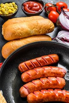 Ingrediënten voor het maken van zelfgemaakte hotdogs. worstjes in de pan, vers gebakken broodjes, mosterd, ketchup, komkommers
